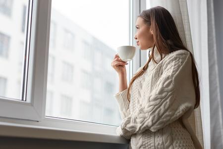 Mujer soñando relajante con bebida en la ventana Foto de archivo