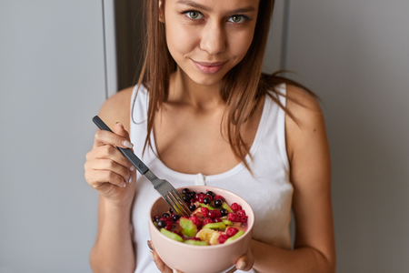Young woman with bowl of fruit salad Stock fotó