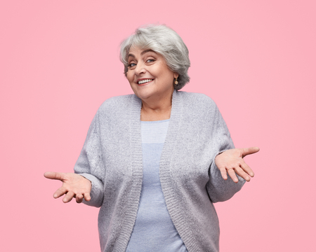 Healthy elderly female shrugging shoulders Stock Photo