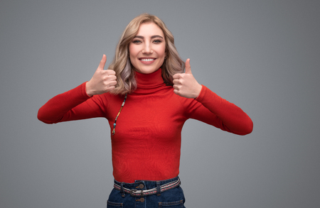 Smiling lady in sweater showing thumb ups