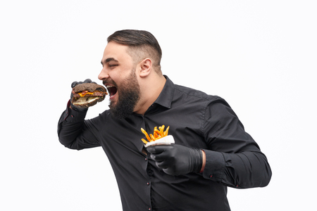 Male with french fries biting burger