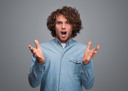 Shocked man with curly hair looking at camera