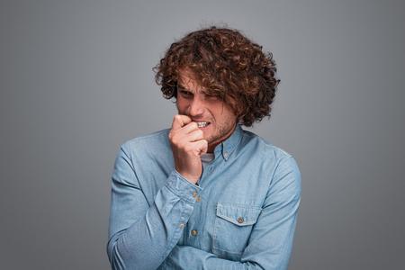 Uomo nervoso che si mangia le unghie