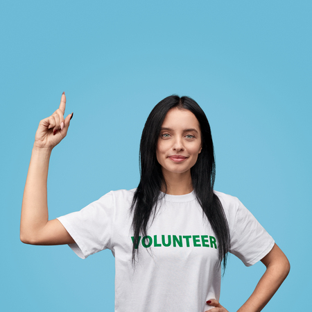 Confident volunteer pointing up Stockfoto