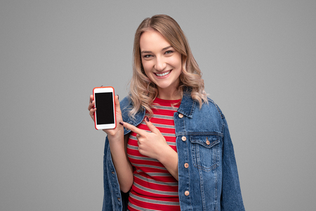 Smiling teenager pointing at smartphone