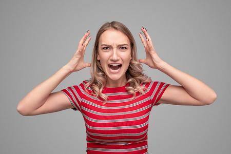 Angry young woman screaming at camera Stock Photo
