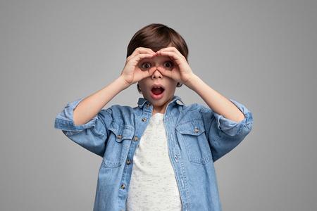 Shocked boy looking at camera through hand binoculars