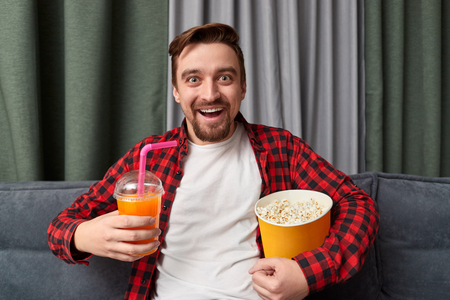 Excited guy with drink and popcorn watching movie