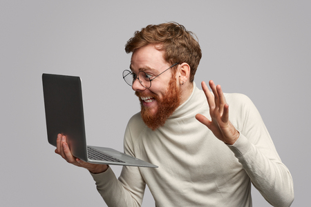 Cheerful man looking at laptop with prize Stock Photo
