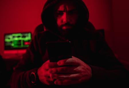 Bearded man using smartphone for hack Banco de Imagens