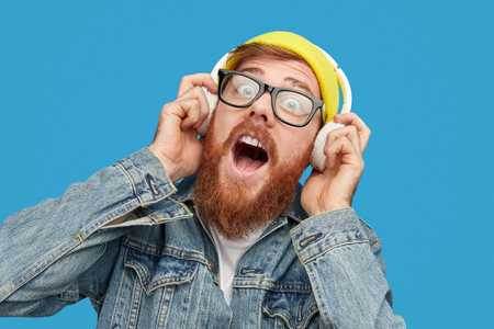 Bearded hipster listening to loud music
