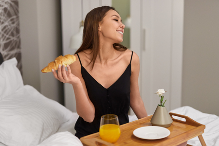 Slim content girl enjoying croissant in bed