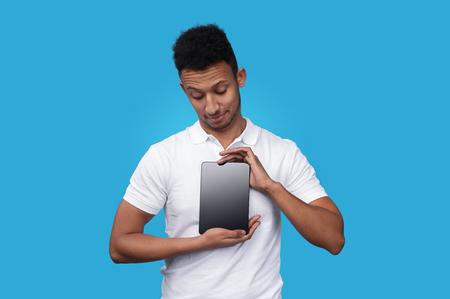 Enchanting ethnic man presenting tablet