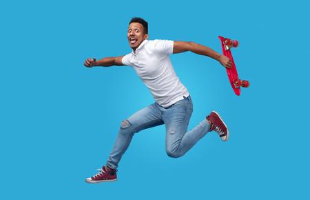 Funny ethnic male jumping with skateboard