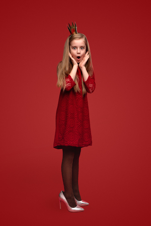 Pequeña princesa sorprendida en zapatos para adultos