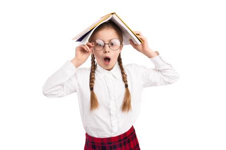 Erstauntes Schulmädchen mit Lehrbuch Standard-Bild