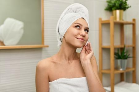 Dreamy girl taking care of face skin 免版税图像