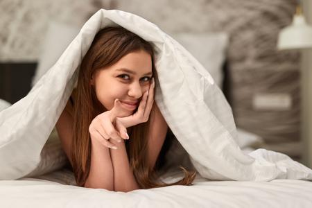 Verleidelijke vrouw die naar bed uitnodigt Stockfoto