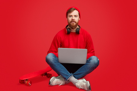 Serious hipster man with laptop and skateboard