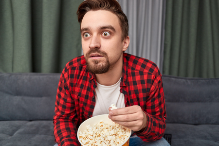 Shocked man eating popcorn and watching movie