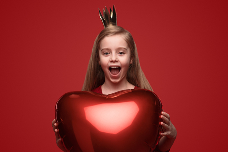 Excited little princess with heart balloon Фото со стока