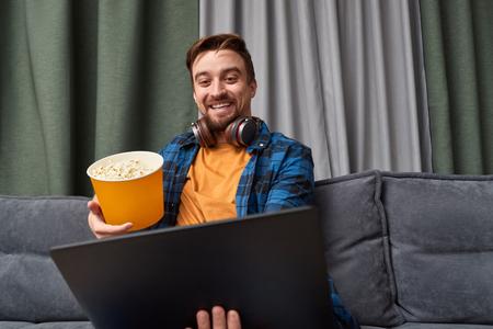 Smiling man watching movie on sofa 写真素材