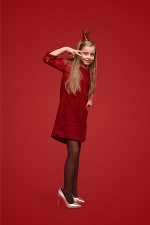 Petite princesse en chaussures stiletto gesticulant signe V