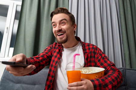 Laughing guy with popcorn and drink watching movie Banco de Imagens