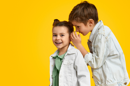 Boy telling secrets to girl Stock Photo
