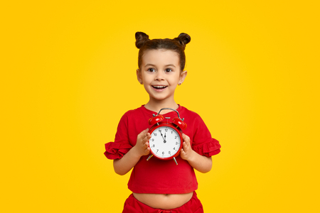 Cheerful girl with alarm clock 写真素材 - 121479952