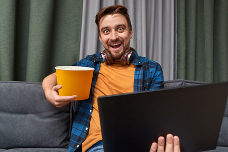 Excited man with popcorn and laptop during movie night Stock fotó