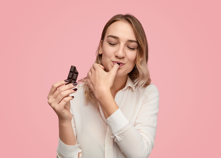 Young woman licking finger with chocolate