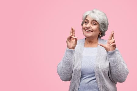 Cheerful elderly woman making wish