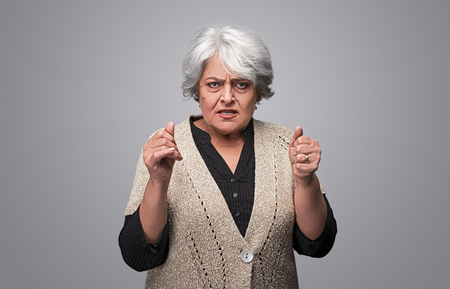 Angry senior female looking at camera Stock Photo