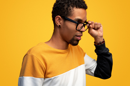 Thoughtful black male adjusting glasses