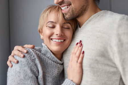 Smiling woman leaning on chest of husband