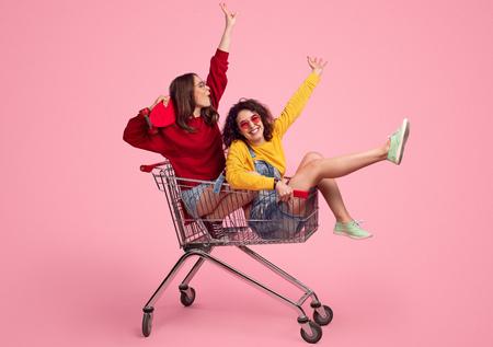 Giovani hipster che cavalcano il carrello della spesa