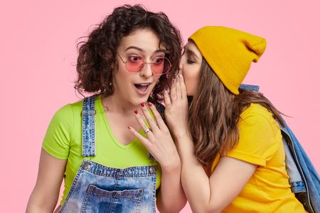 Jeune femme disant secret à un ami