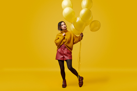 Trendy woman with yellow balloons
