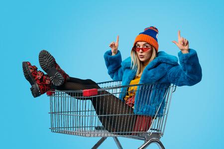 Vreemde vrouw in winkelwagen die naar boven wijst