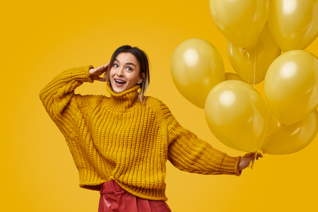 Cheerful woman with balloons saluting