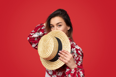 Trendy woman hiding face behind hat