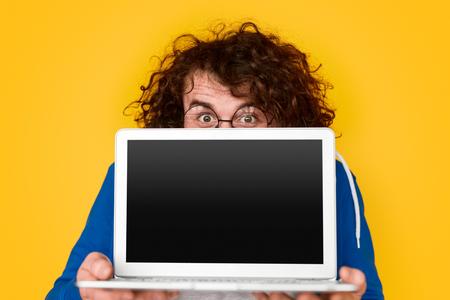 Funny nerdy guy showing blank laptop Banco de Imagens