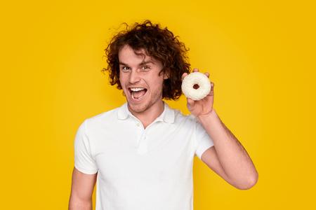 Cheerful guy enjoying sweet donut Stock Photo - 124093820