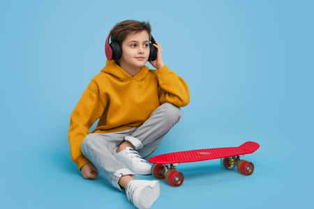 Stylish boy listening to music near skateboard