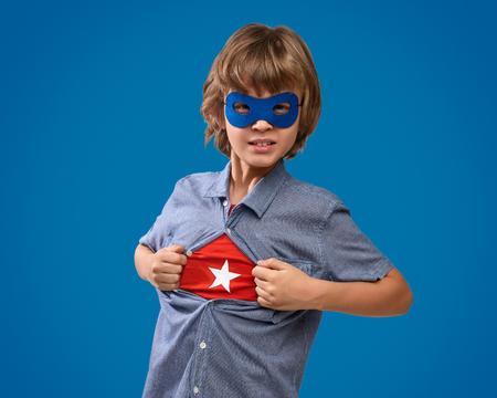Garçon confiant montrant l'emblème de super-héros