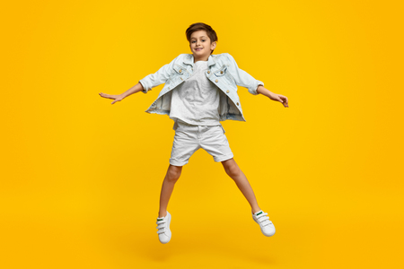 Smiling youngster in stylish outfit leaping up