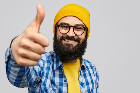 Confident hipster gesturing thumb up Standard-Bild