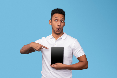 Surprised black male pointing at tablet with blank screen 스톡 콘텐츠