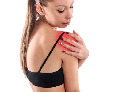 Young woman massaging aching shoulder